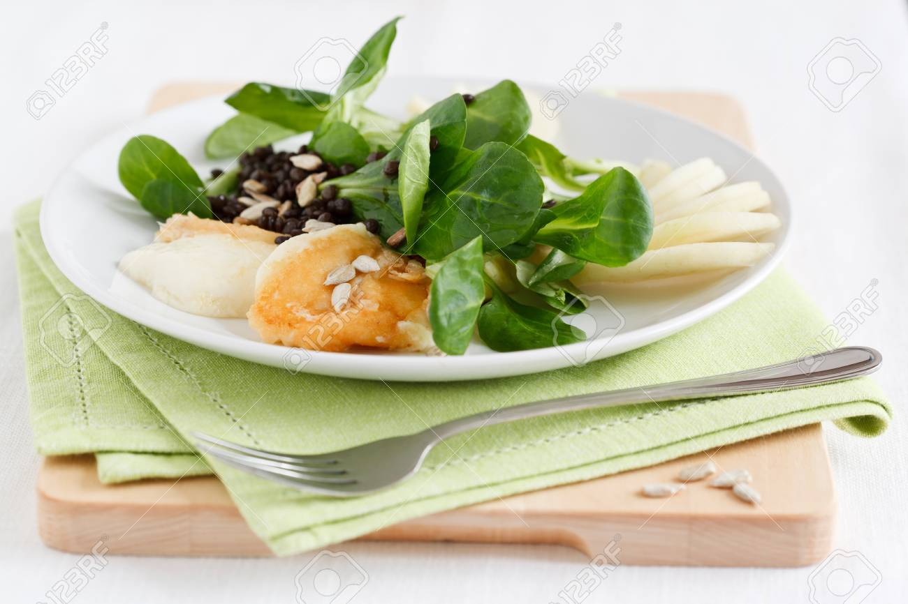 Valerianella with fried halloumi cheese, pears and black lentils, served on a plate with a green napkin. Stock Photo - 11177324