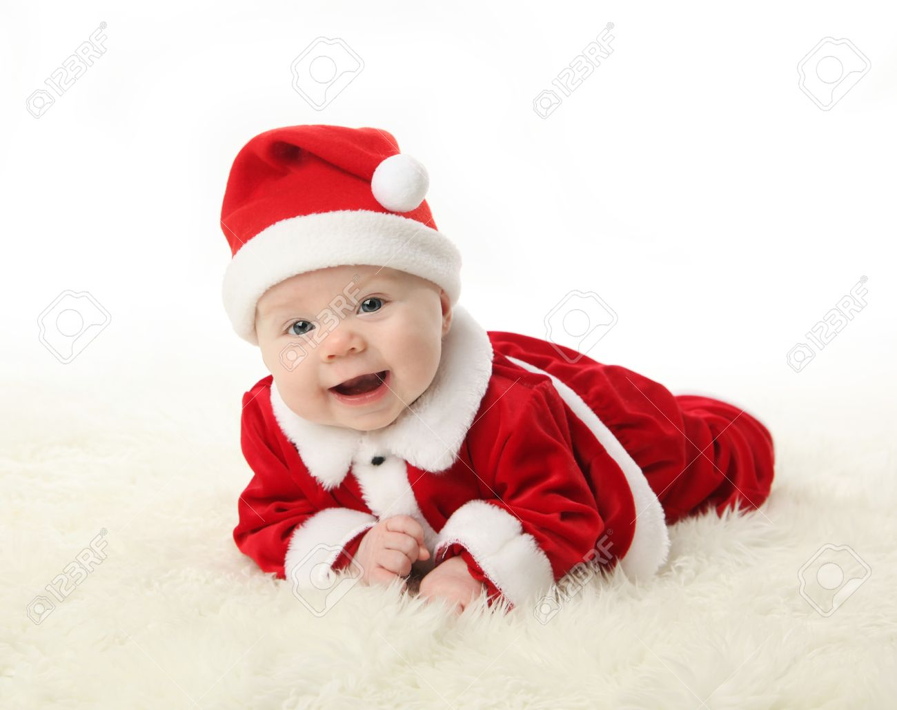6c3532ff9d5 Happy smilng baby lying on tummy wearing a red and white Christmas Santa hat  and suit
