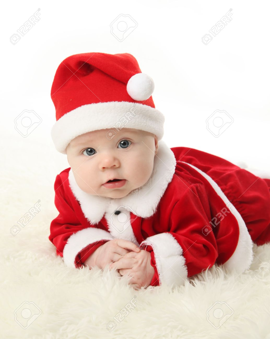 Baby lying on tummy wearing a red and white Christmas Santa hat and suit, isolated on a white background. Stock Photo - 8382886