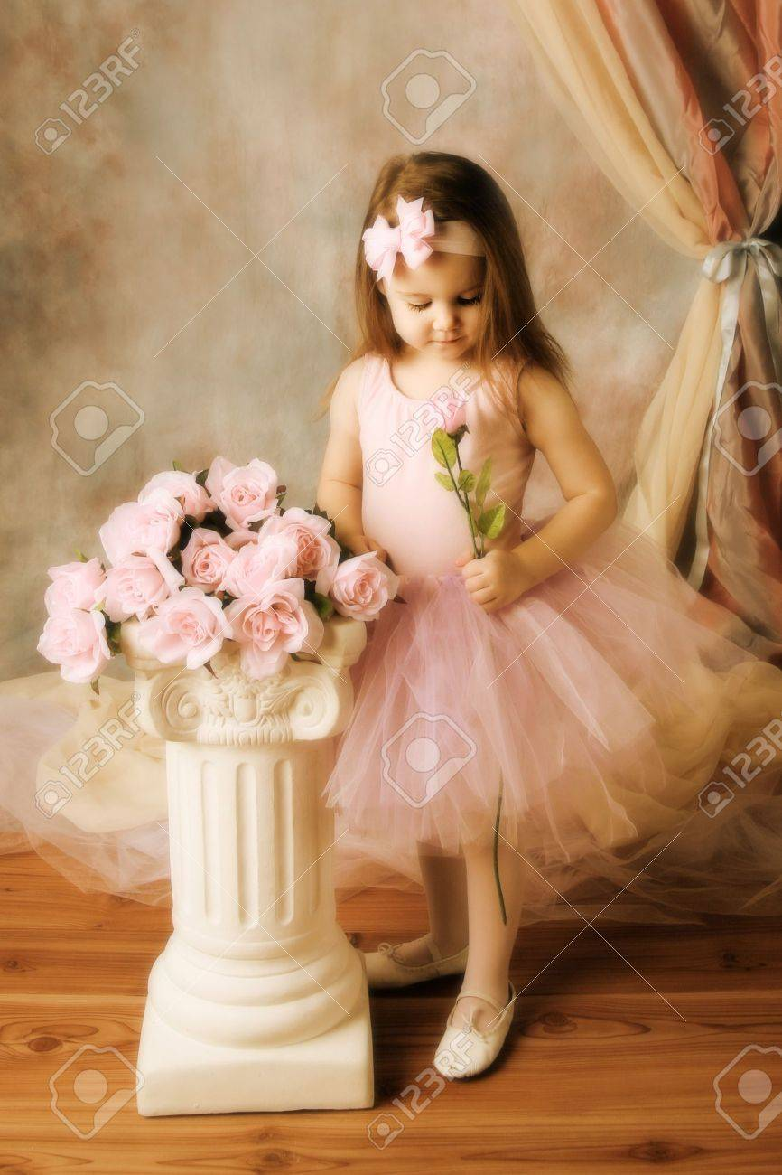 Adorable little girl dressed as a ballerina in a tutu standing next to pink roses. Stock Photo - 8534015
