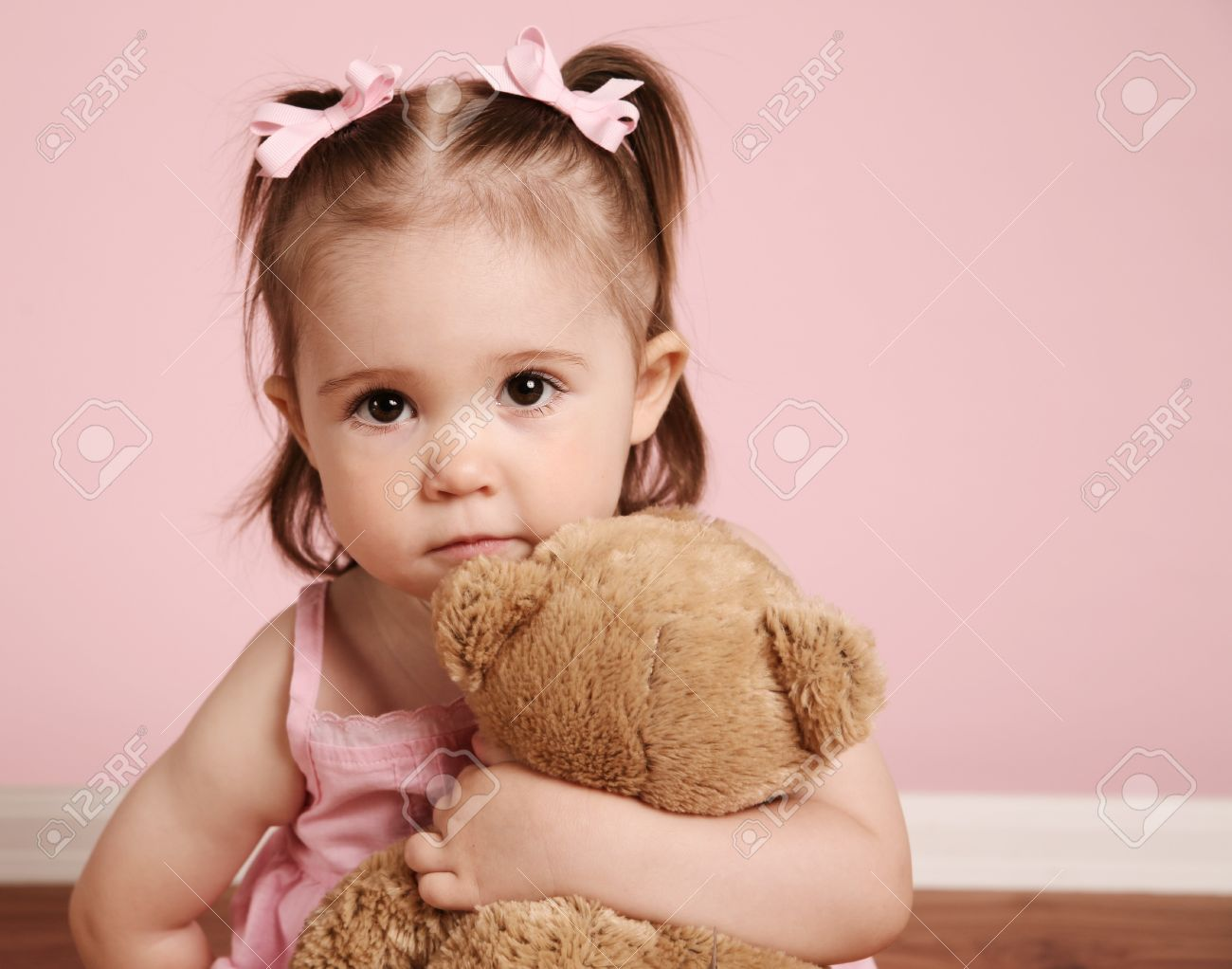Portrait of an adorable toddler girl hugging a teddy bear on a vintage pink background - 8710185