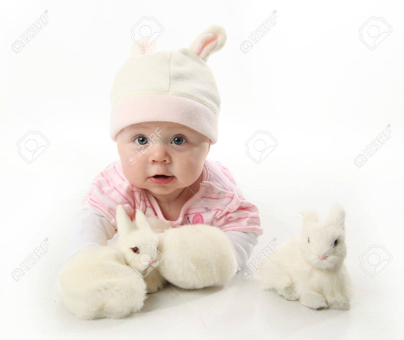 Portrait of an adorable baby girl wearing a bunny rabbit costume and petting two white bunnies Stock Photo - 8710142
