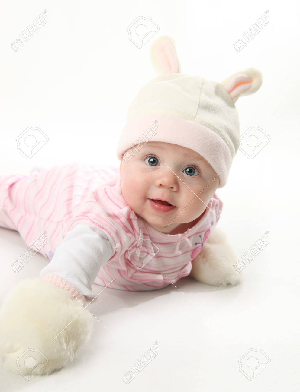 Portrait of an adorable baby girl wearing a bunny rabbit costume and furry mittens - 8710180