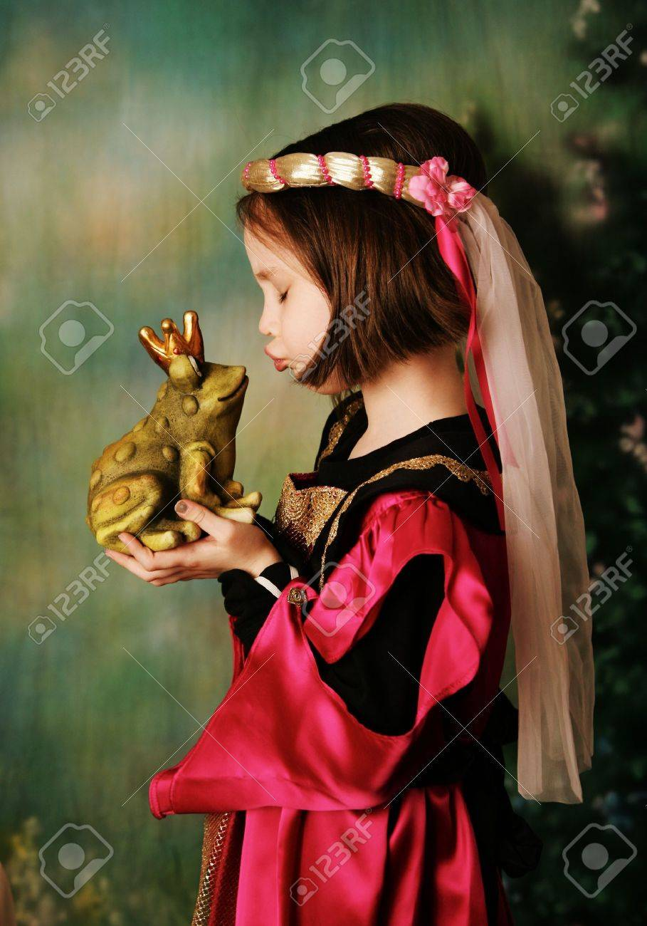 Portrait of a cute young preschool girl dressed as a princess in a pink and gold gown, posing and kissing a frog prince wearing a crown - 8710221