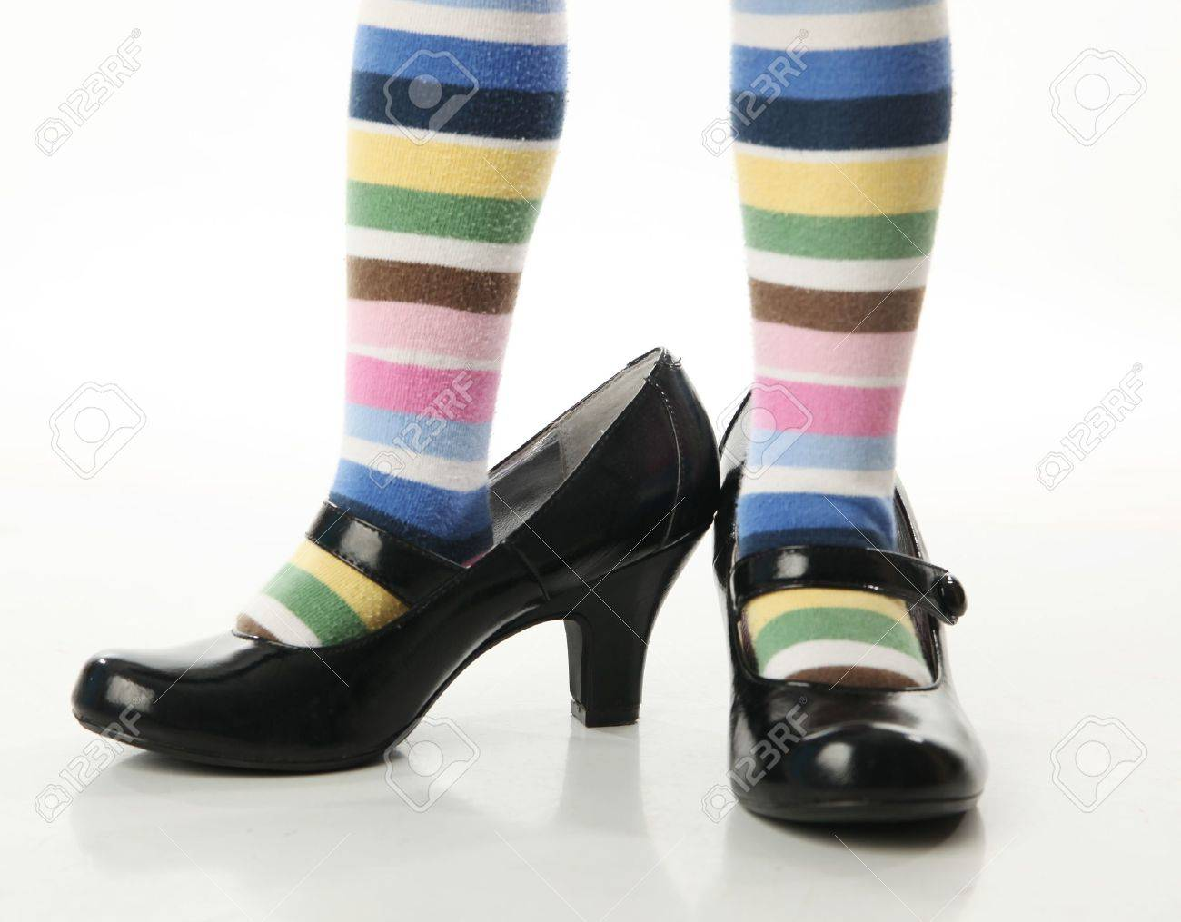Toddler girl wearing bright colored striped tights trying on mother's high heel shoes - 8809253