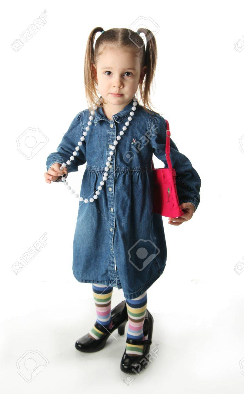 Portrait of an adorable preschool girl playing dress up with a mother's shoes, purse, and pearl necklace isolated on white - 8809252