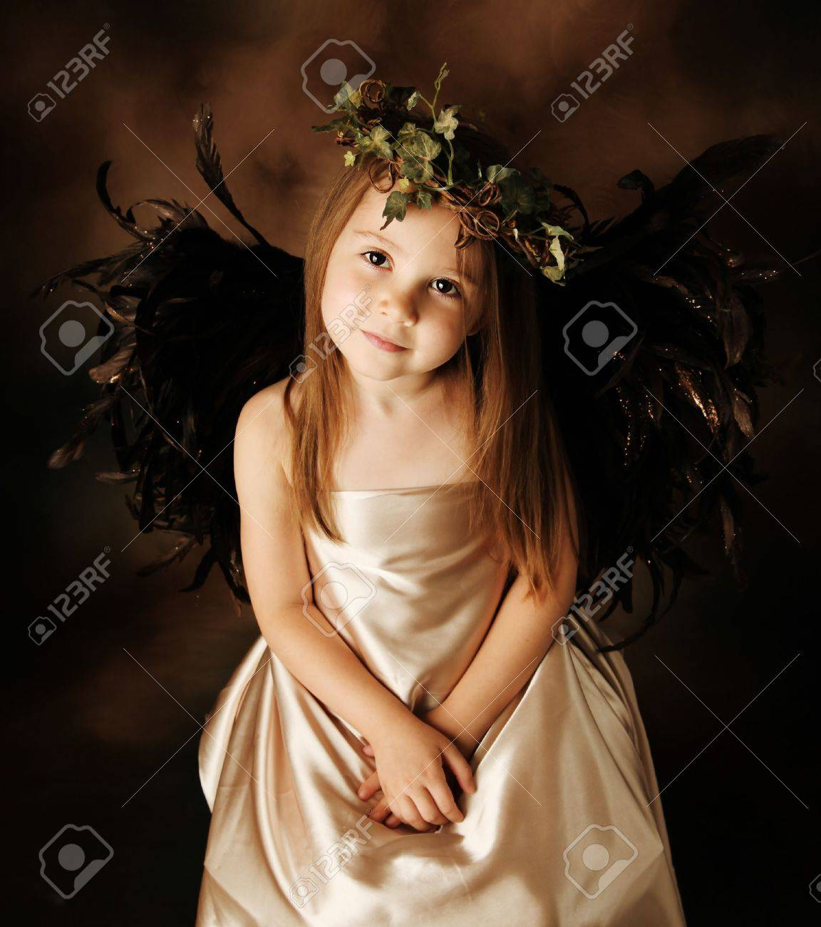 Portrait of a beautiful young girl dressed up as an angel with brown wings and a gold dress, wearing an ivy crown - 8809349