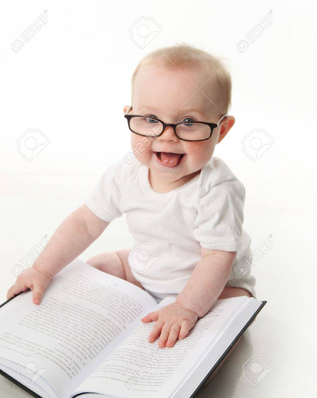 5438e92587 Foto de archivo - Retrato de un adorable bebé sentado uso de anteojos y  mirando a un libro, aislado en blanco