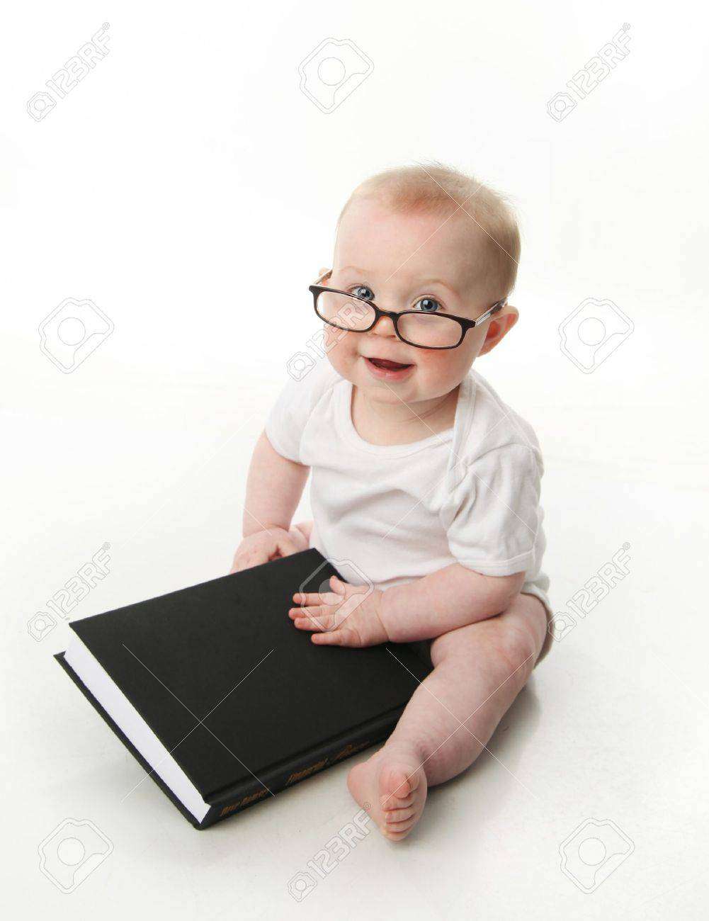 Portrait of an adorable baby sitting up wearing eyeglasses and looking at a book, isolated on white - 9939636