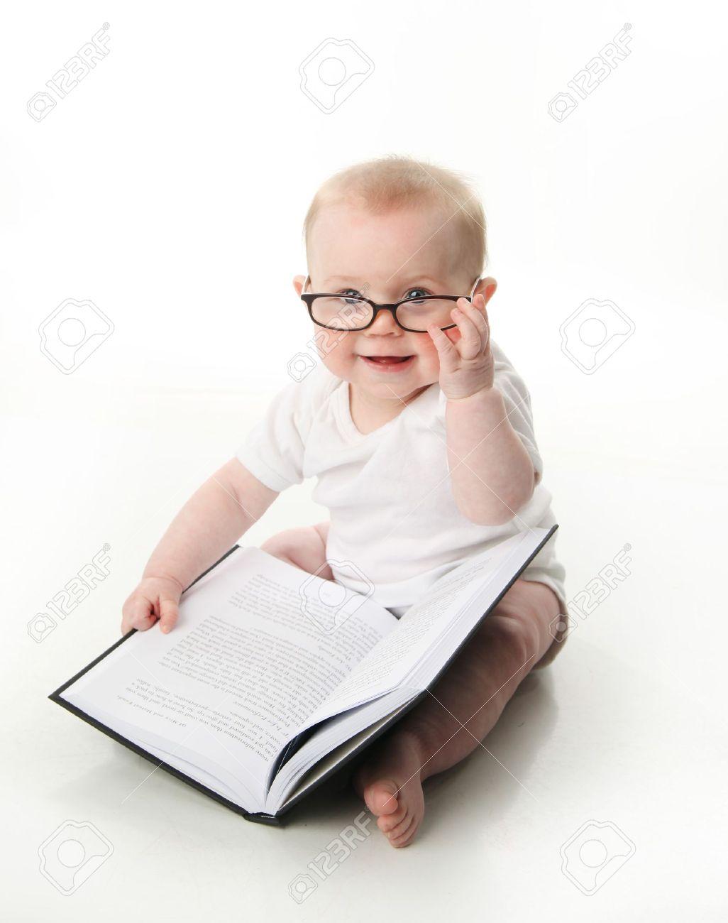 e8a173be68 Foto de archivo - Retrato de un adorable bebé sentado llevaba anteojos y  mirando un libro, aislado en blanco