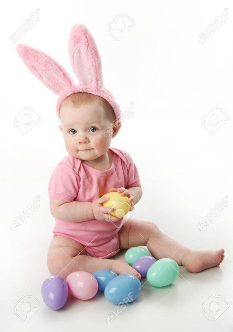 Portrait of a cute baby dressed in Easter bunny ears with a basket full of eggs - 9939701