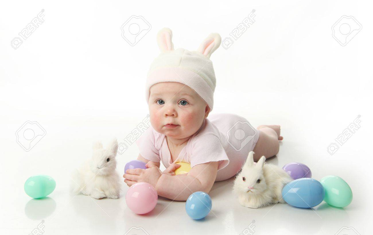 Portrait of a cute baby dressed in Easter bunny ears with pastel eggs - 9939643