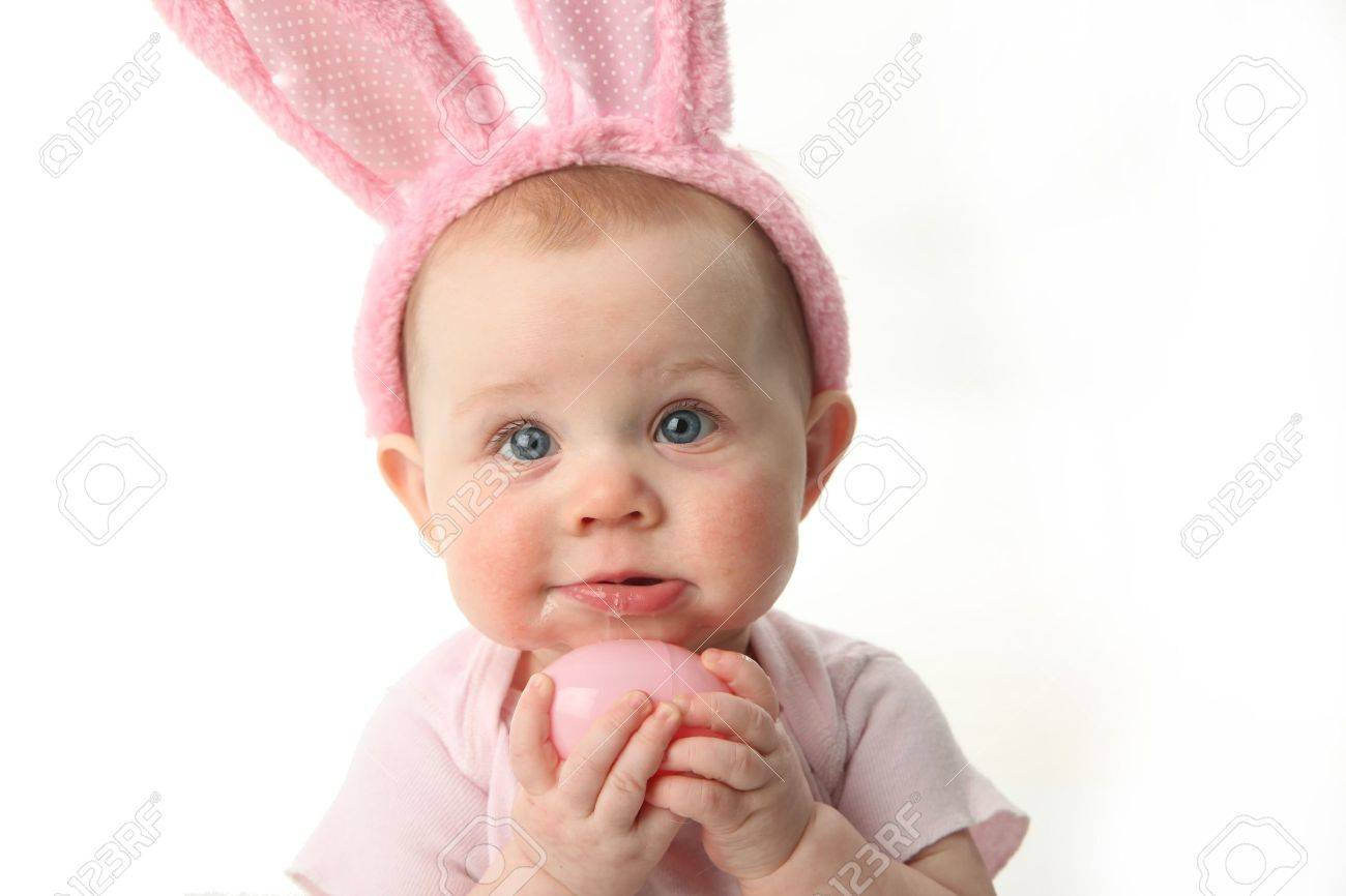 Portrait of a cute baby dressed in Easter bunny ears pastel eggs - 9939664