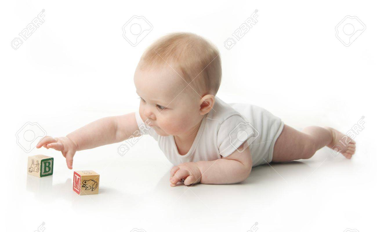 Portrait of a cute baby sitting playing with wooden blocks - 9939525