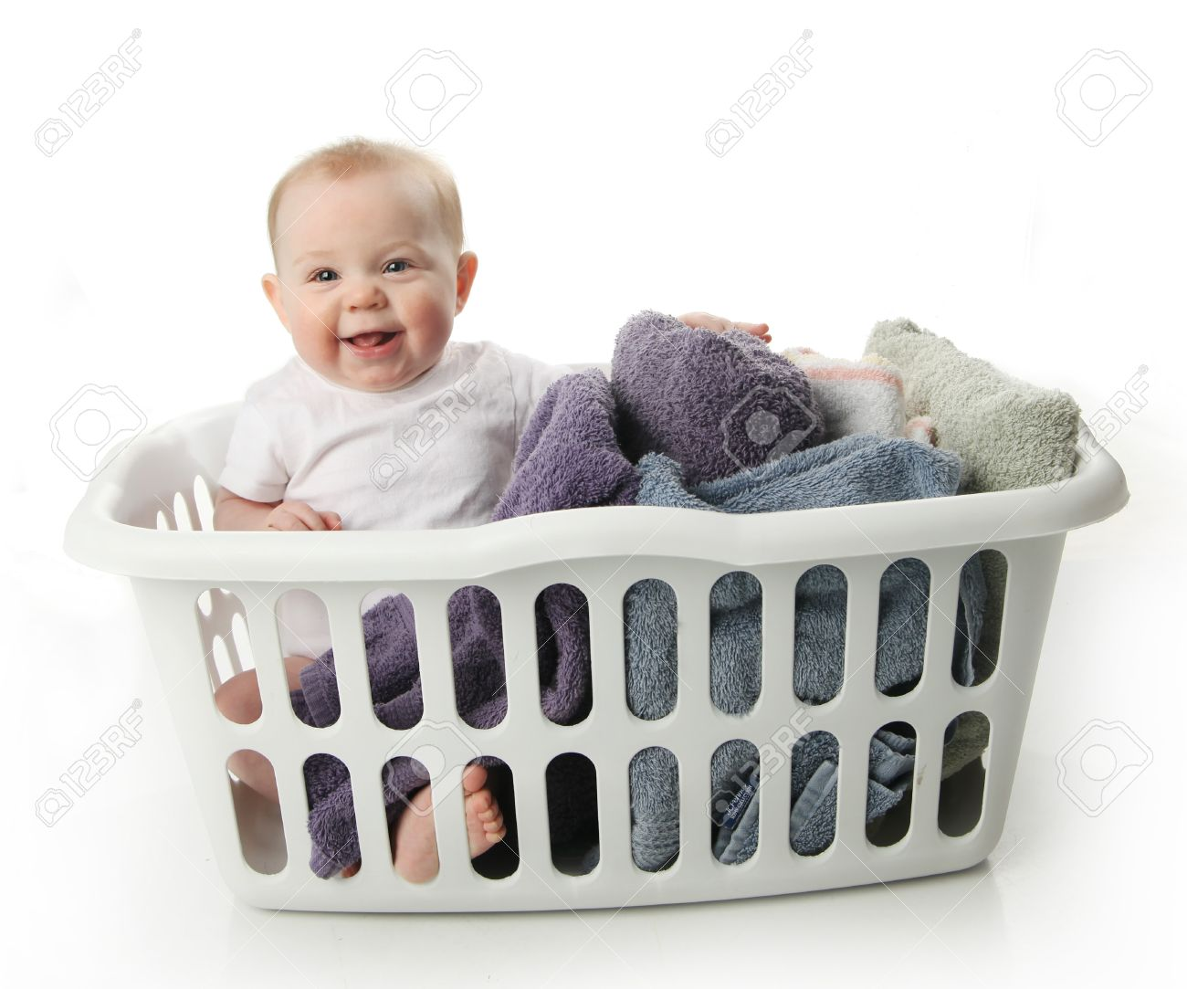Portrait of an adorable baby sitting in a laundry basket with towels - 9939571