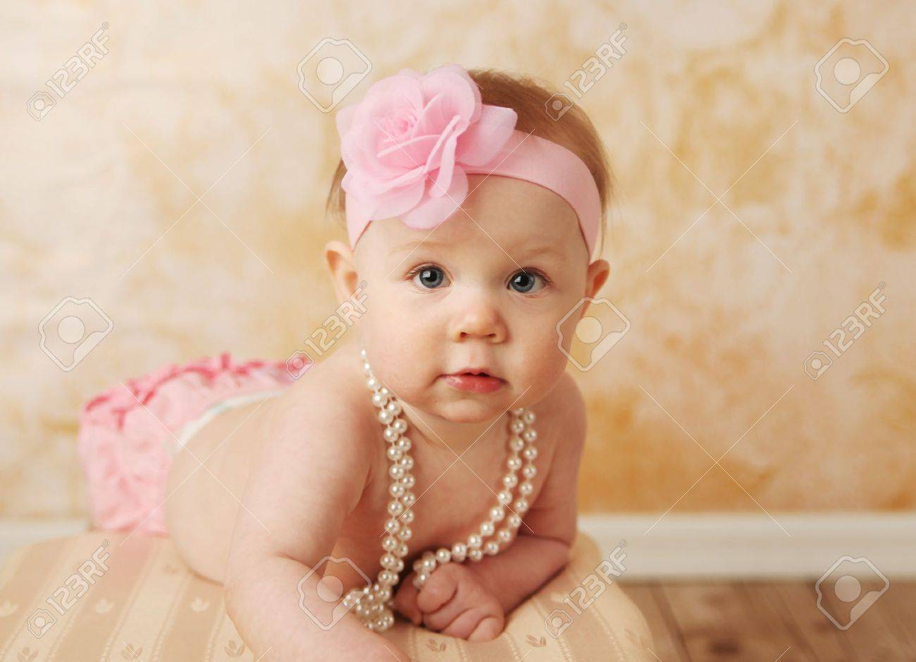 adorable young baby girl wearing a vintage pearl necklace and