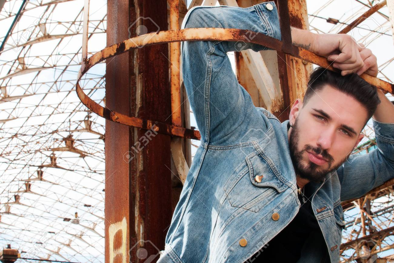 Young Man On A Ladder With Denim Jacket Black Shirt And Pants