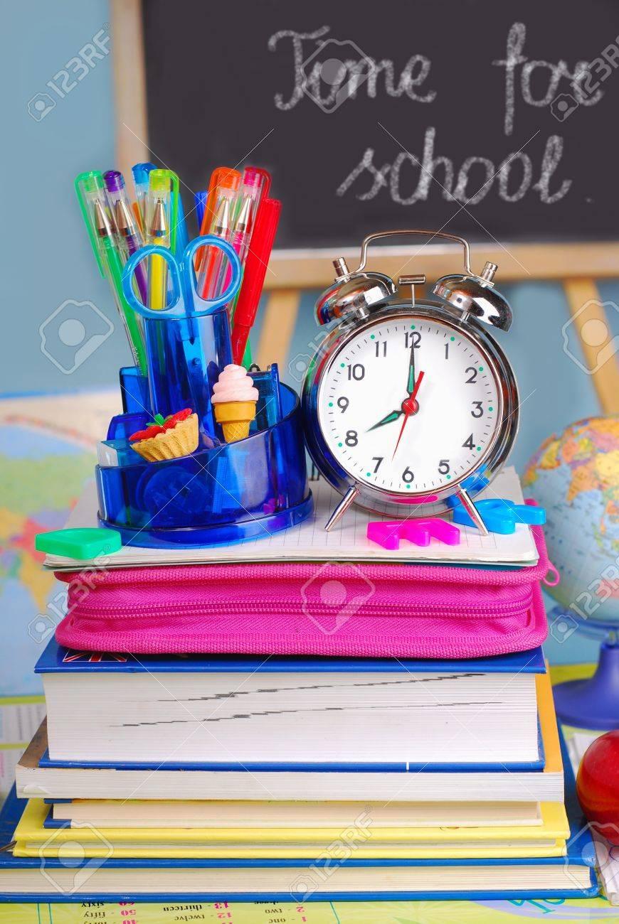 school equipment and retro alarm clock on the desk in the classroom Stock Photo - 10281363