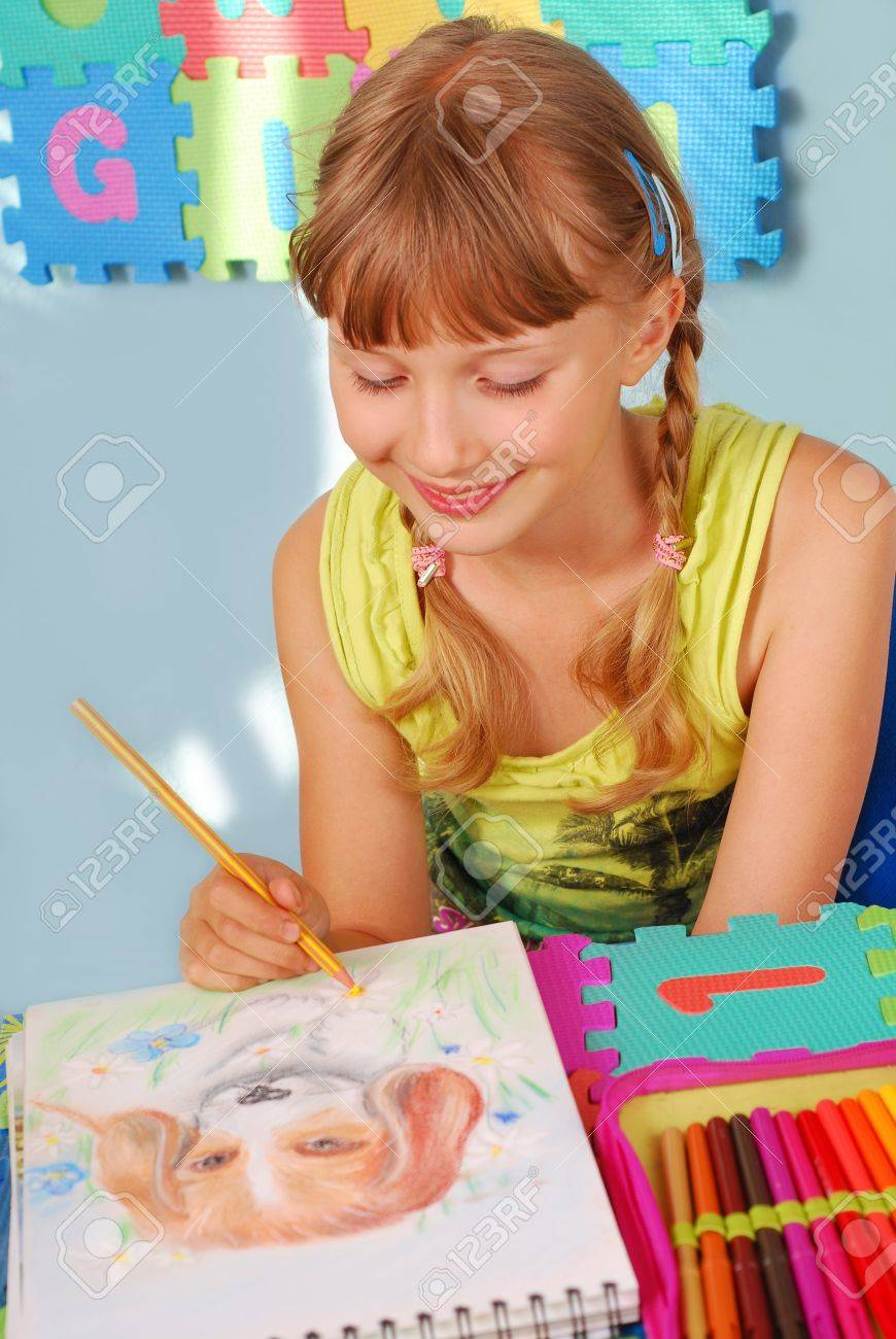 young girl drawing a picture of dog with colored pencils sitting in the room Stock Photo - 10365241