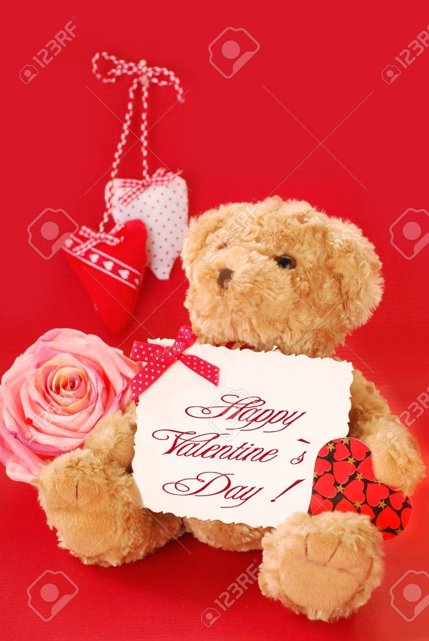 teddy bear holding a card with valentine`s greetings against red background Stock Photo - 11872484