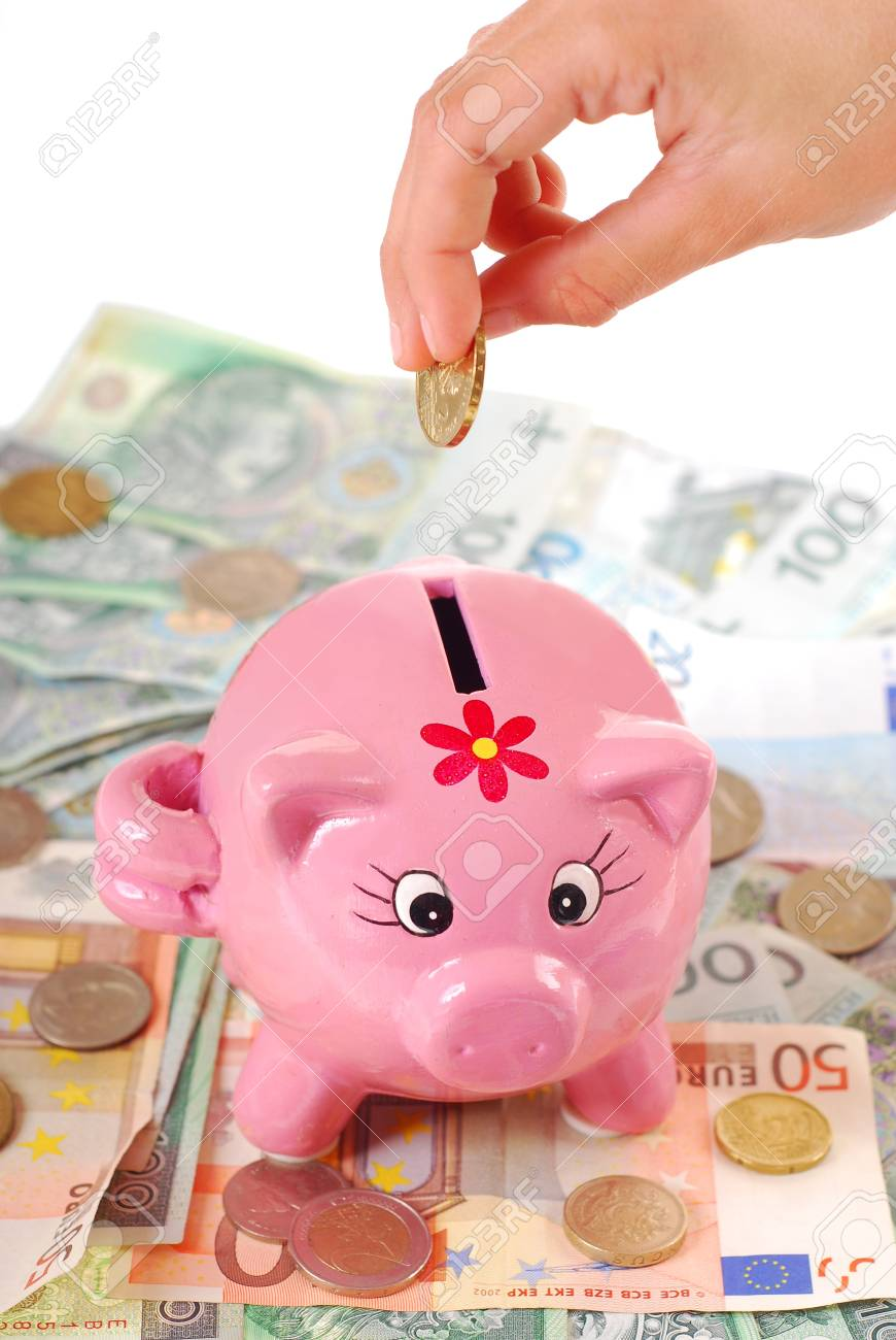 hand  throwing the coin into pink piggy bank standing on banknotes background Stock Photo - 14800947