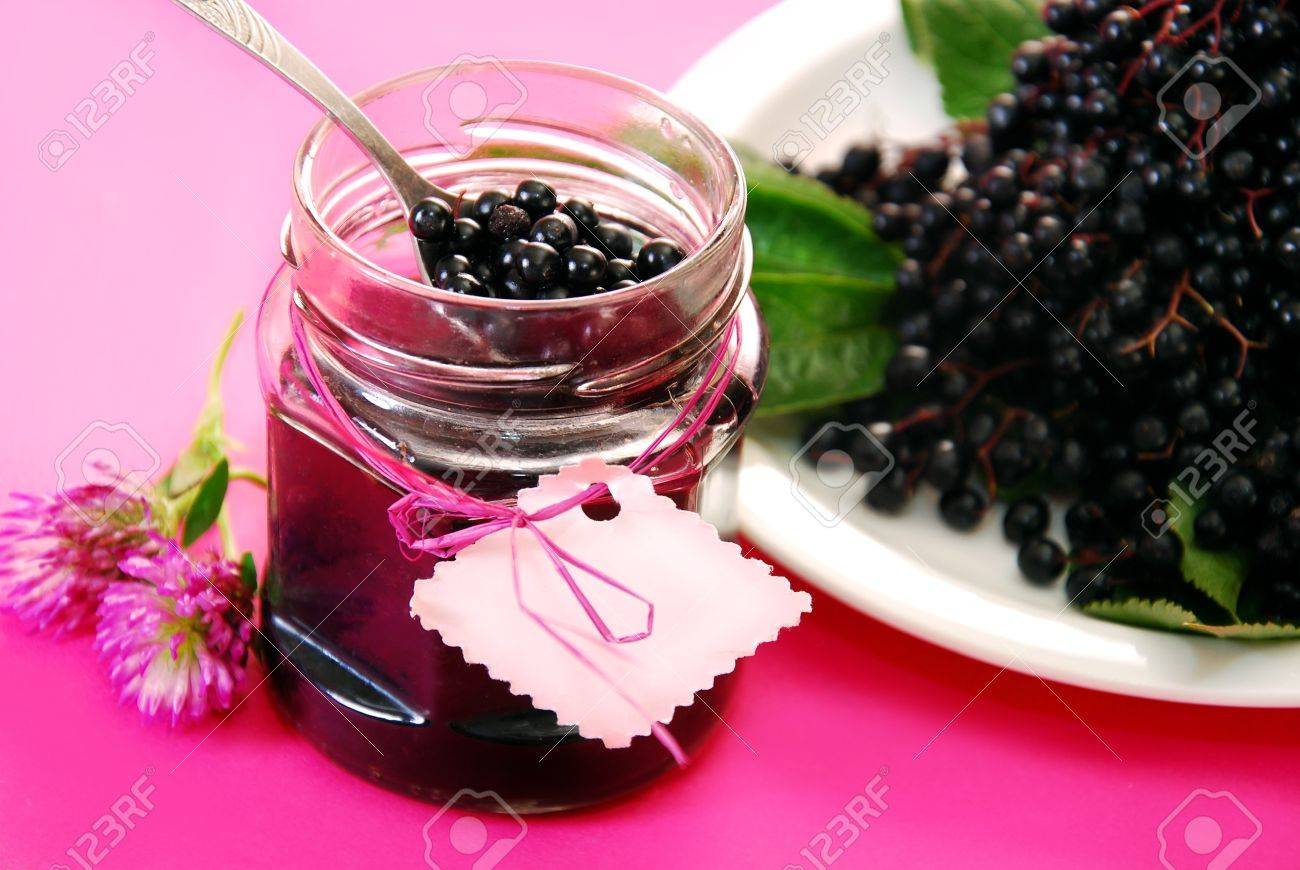 jar of homemade elderberry confiture and fresh fruits on pink background - 15681812