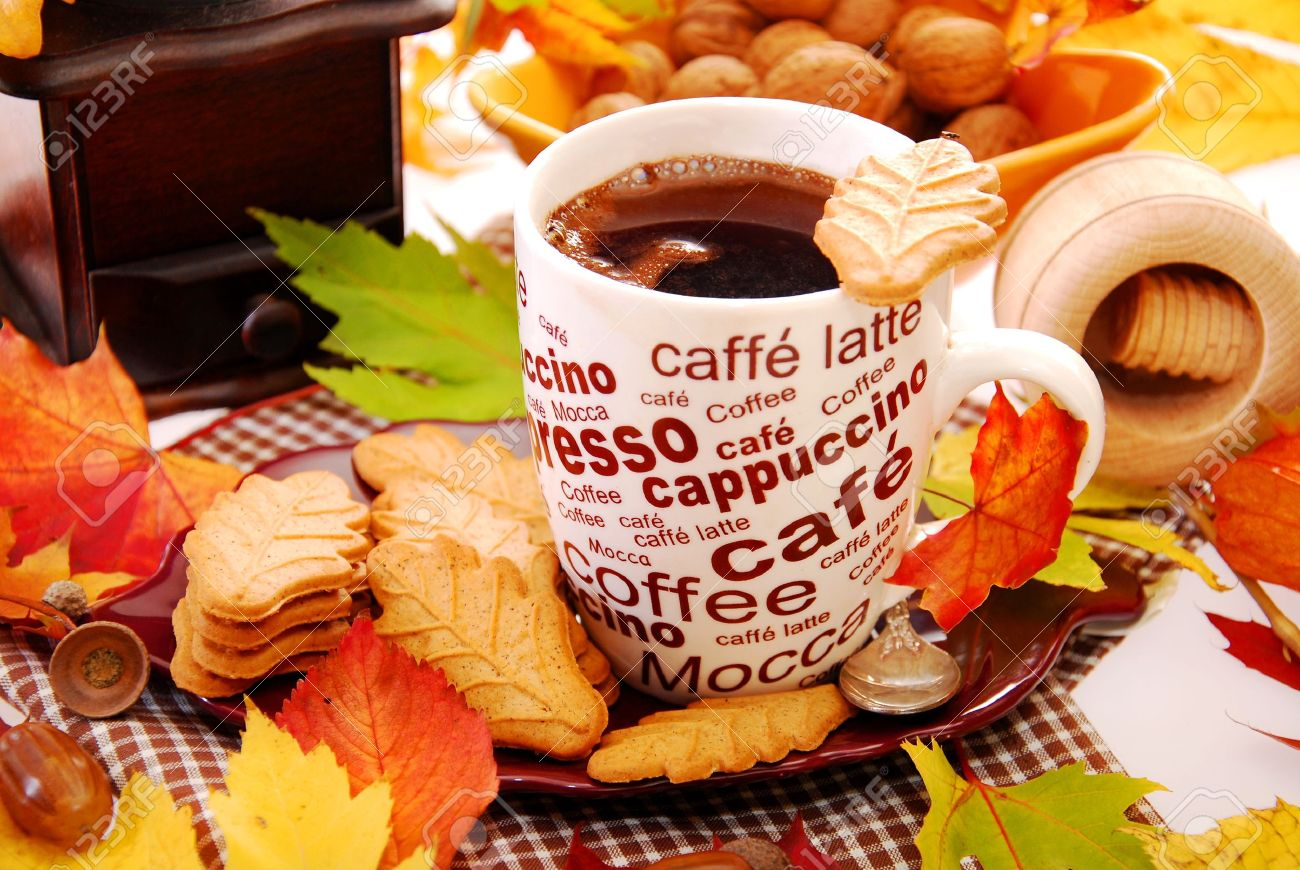 cup of coffee and cookies in leaf shape on table with autumn decoration - 15914938