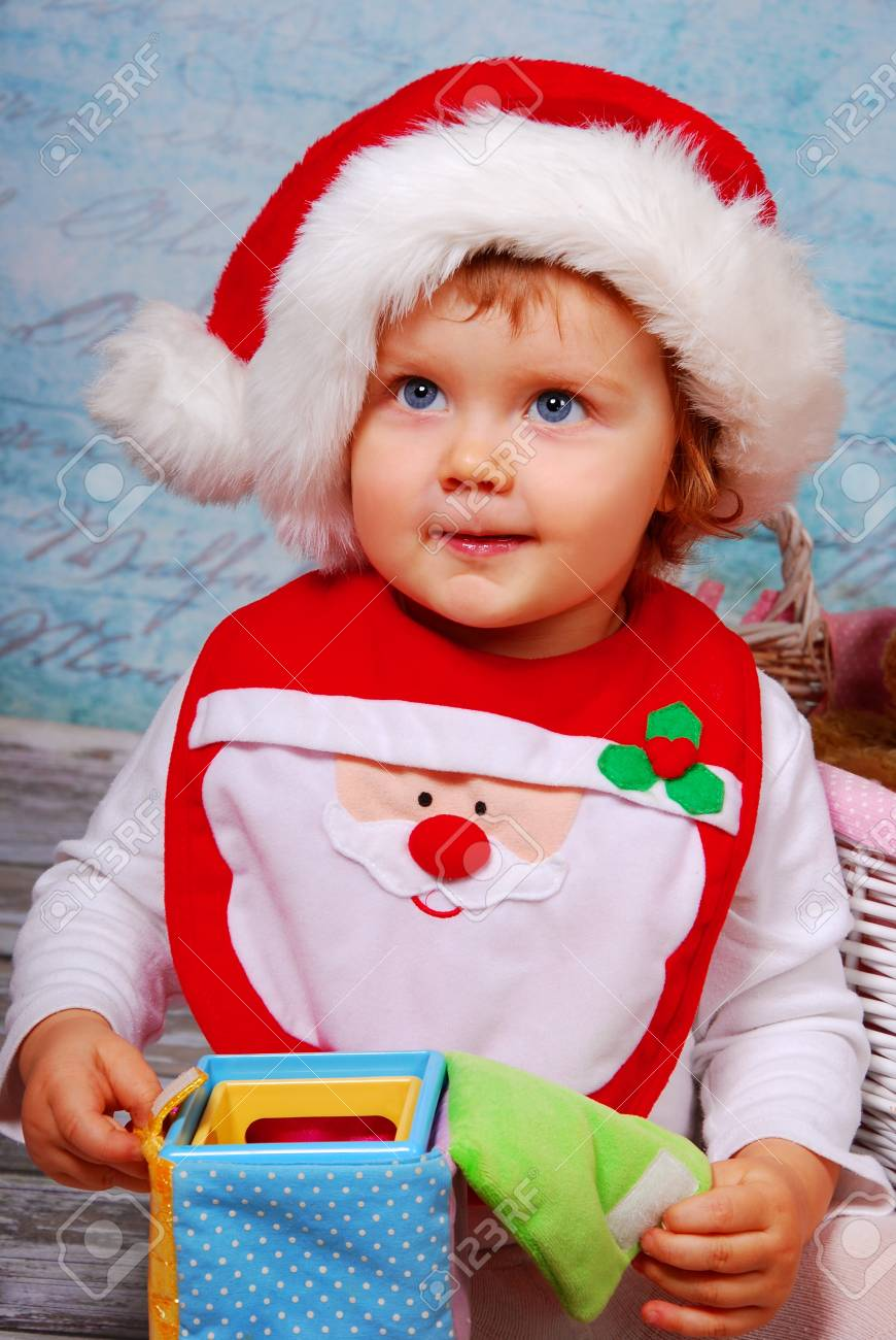 afdb4daa3 portrait of cute baby girl in red santa hat playing with toys Stock Photo -  16828069