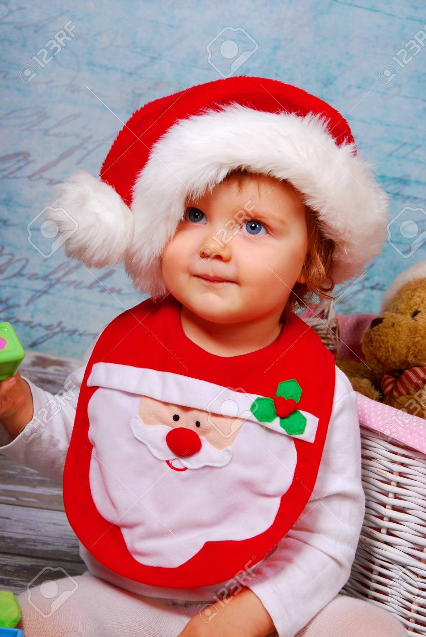 a0f09ff03 portrait of cute baby girl in red santa hat playing with toys Stock Photo -  16828068