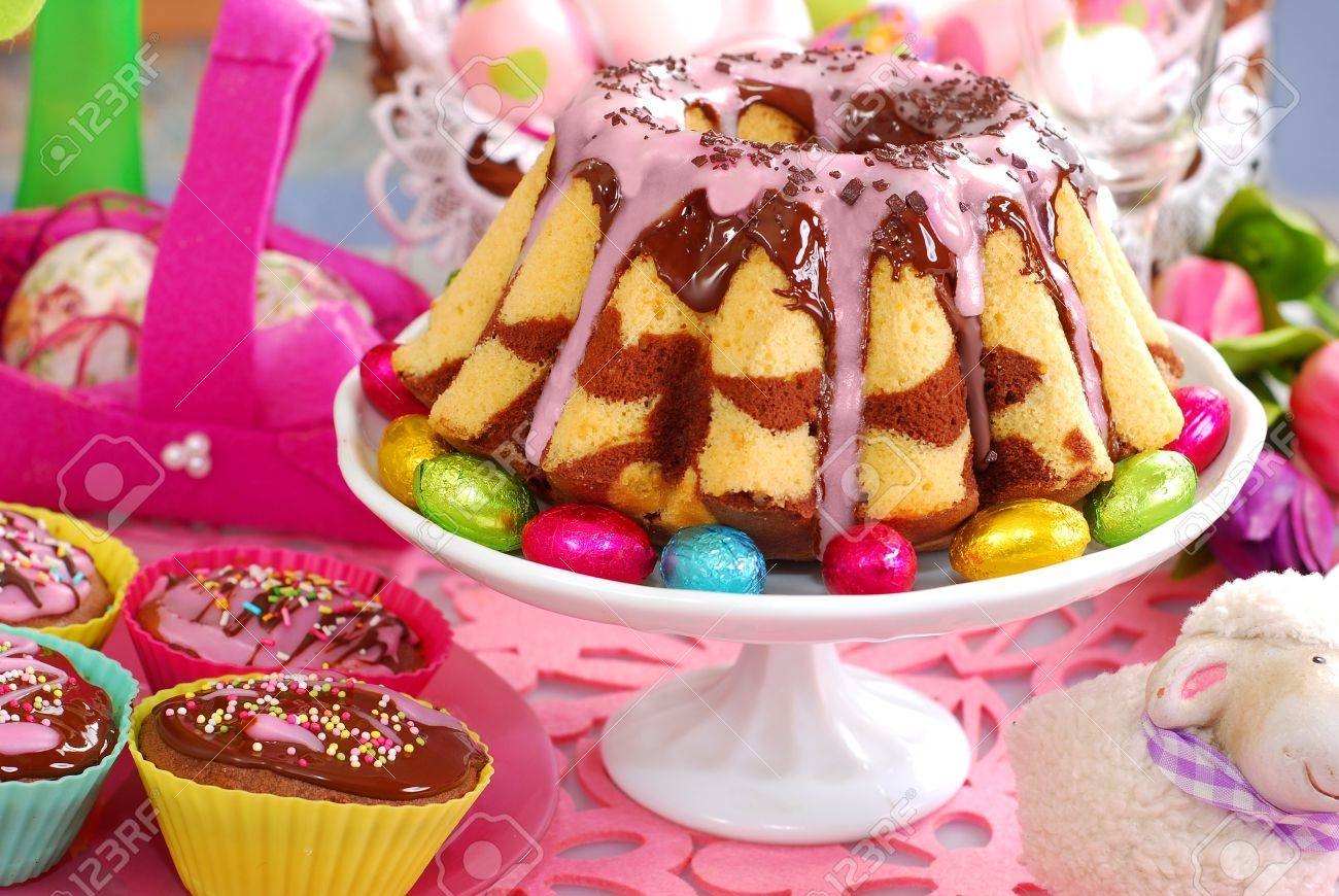 homemade marble ring cake poured chocolate sauce and pink icing on easter table - 18419174