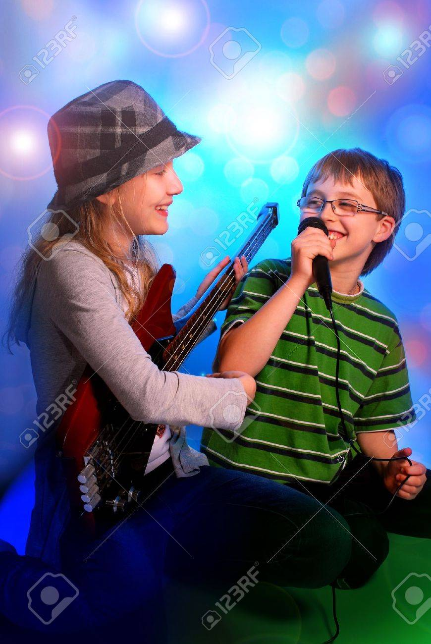 young girl playing the bass guitar and boy singing with microphone on stage - 19428858