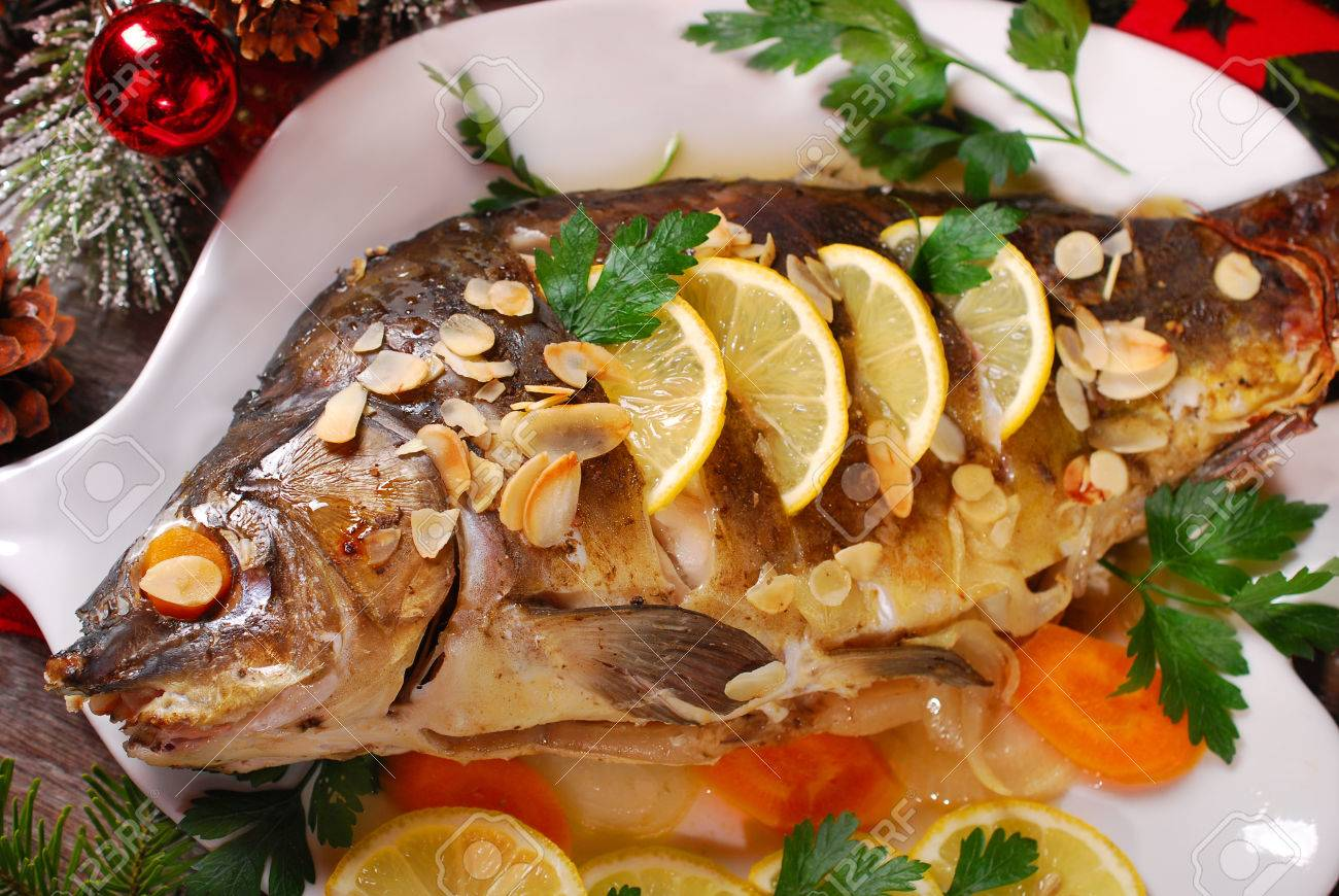 roasted whole carp stuffed with vegetables and almonds on wooden table for christmas - 34558555