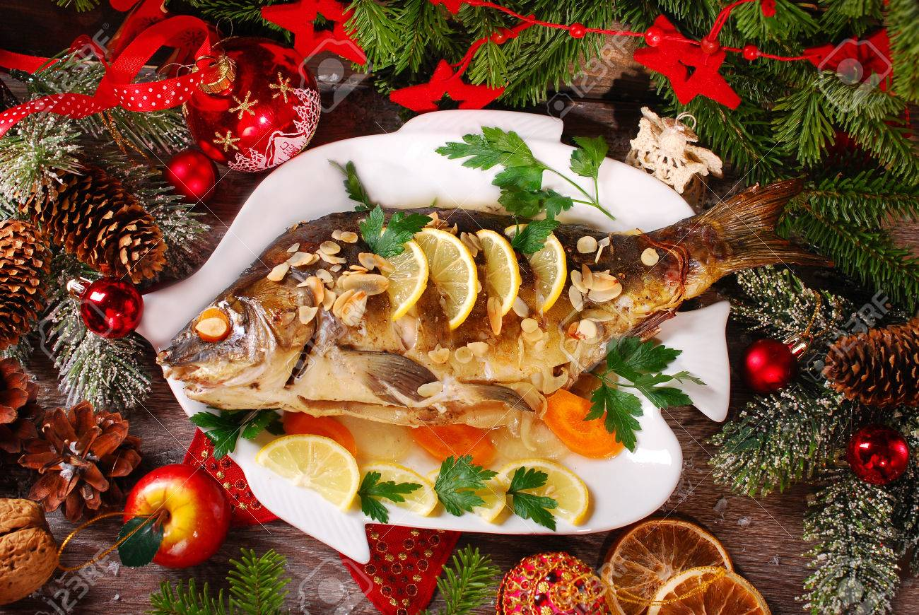roasted whole carp stuffed with vegetables and almonds on wooden table for christmas-top view - 34558556