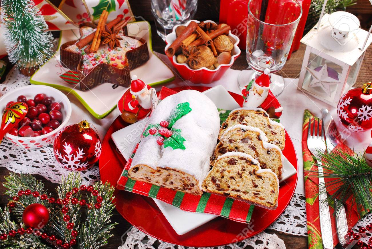 christmas stollen cake partly sliced with dried fruits and marzipan on festive table - 49390391