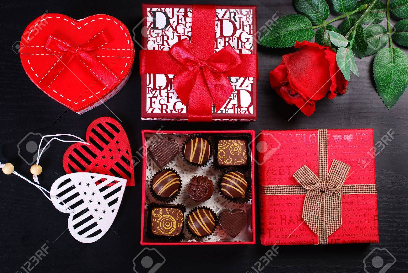red gift boxes with chocolate pralines and rose on black background for valentines day - 52549194