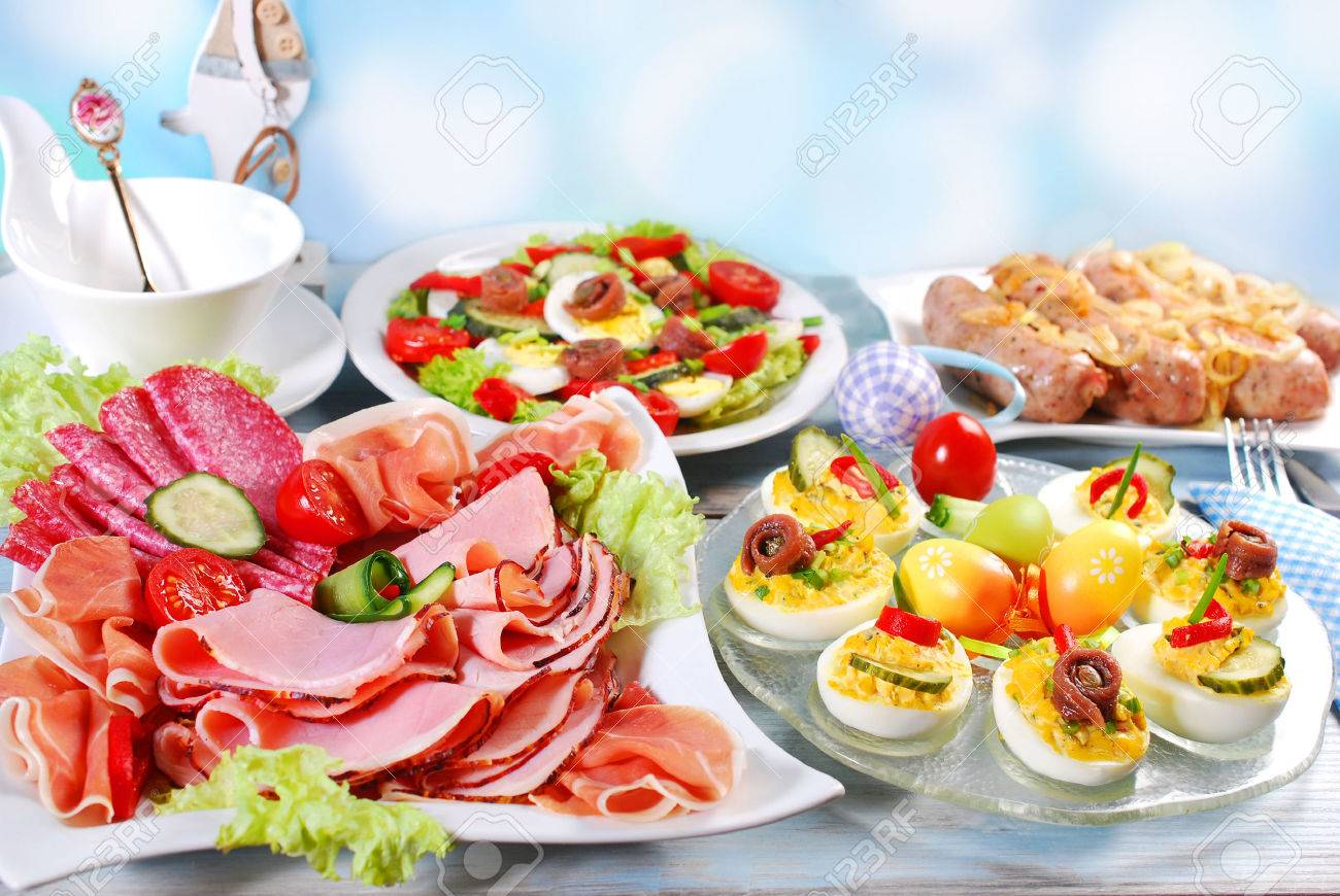 traditional easter breakfast with stuffed eggs,ham and cured meat platter,salad and white sausage with onion - 52549238