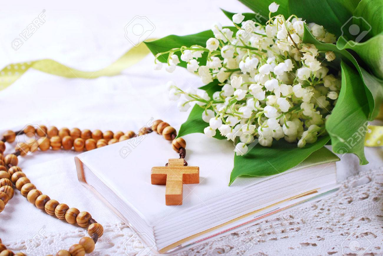 the first holy communion with wooden rosary,prayer book and bunch of lily of the valley - 57802060