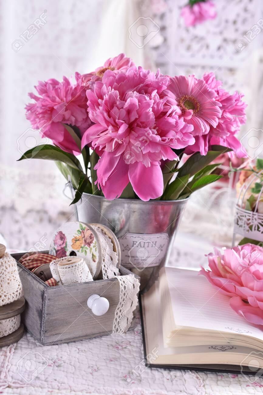 bunch of pink peonies and gerberas in vintage style bedroom - 127582624