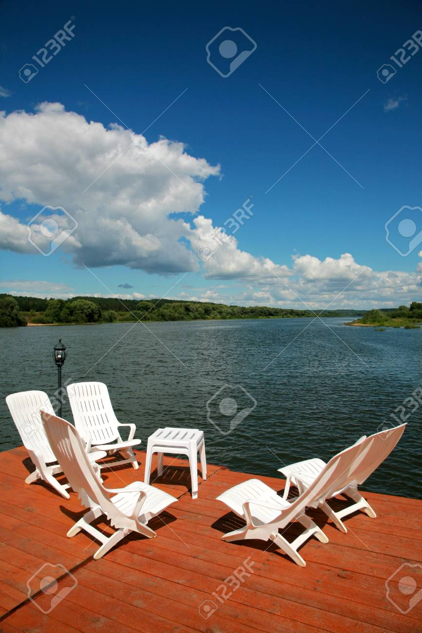 White plastic armchairs on coast of the river Stock Photo - 1319830