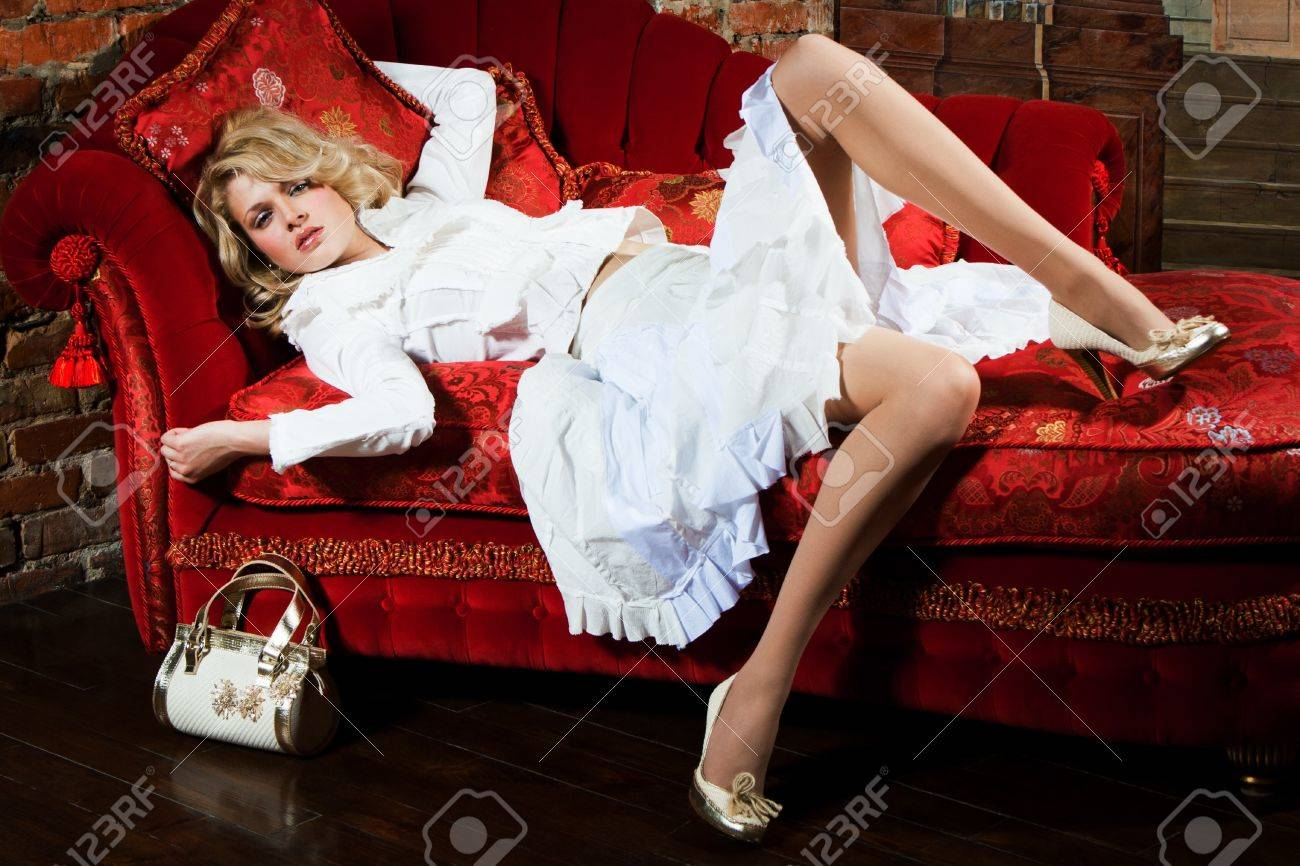 girl in a white dress on the red couch Stock Photo - 8755365