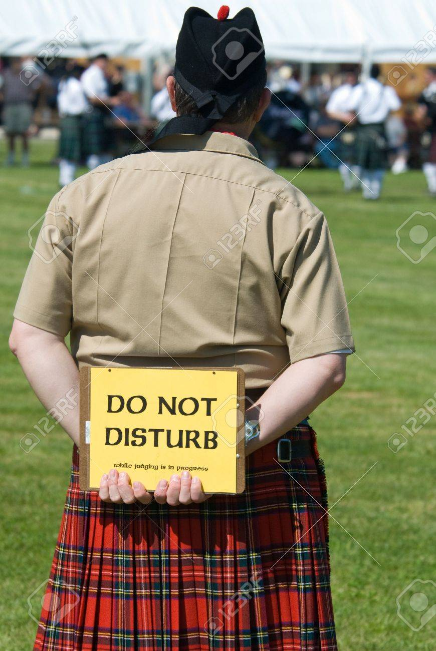 judge at the scottish games parade competition wearing a kilt