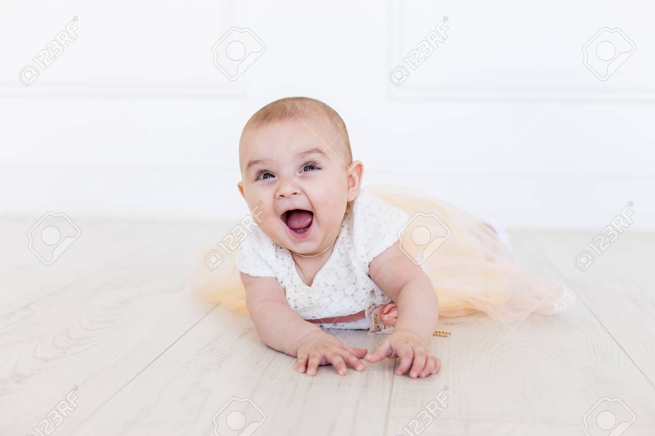 a035b7f44 Happy baby looking at camera. Smiling Infant Baby 6 Month Old. Cute little  girl in modern clothes. Happy baby