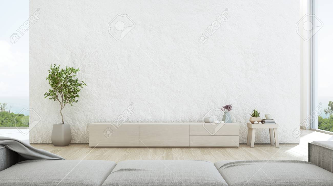 Sea view living room of luxury summer beach house with TV stand and wooden cabinet. Empty rough white concrete wall background in vacation home or holiday villa. Hotel interior 3d illustration. - 103680170