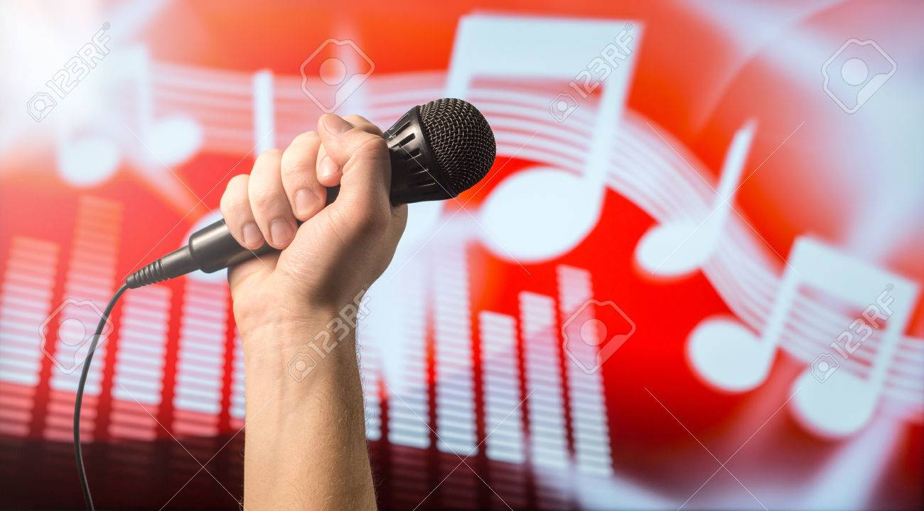 Singing, karaoke or vocal training concept. Microphone in hand in front of an abstract music themed note and equalizer background. Song contest and live performance vibe with copy space for text. - 81109472