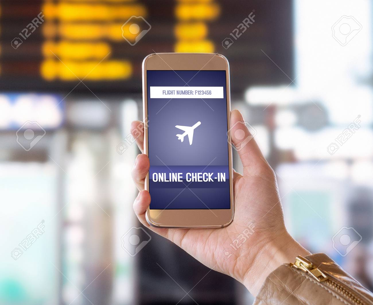 Online check in with mobile phone in airport. Woman checking in to flight with smartphone on the web. Internet self service provided by airline. Hand holding cellphone. Timetable in the background. - 81115996