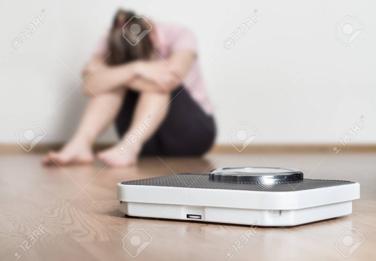 Weight loss fail concept. Scale and depressed, frustrated and sad woman sitting on floor holding head and arms on knees. - 95475352