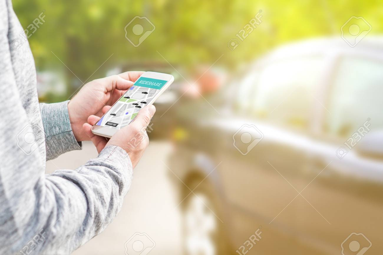 Online ride sharing and carpool mobile application. Rideshare taxi app on smartphone screen. Modern people and commuter transportation service. Man holding phone with a car in background. - 95505309