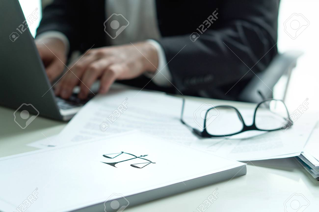 Lawyer working in office. Attorney writing a legal document with laptop computer. Glasses on table. Pile of paper with scale and justice symbol. Law firm and business concept. - 95505442