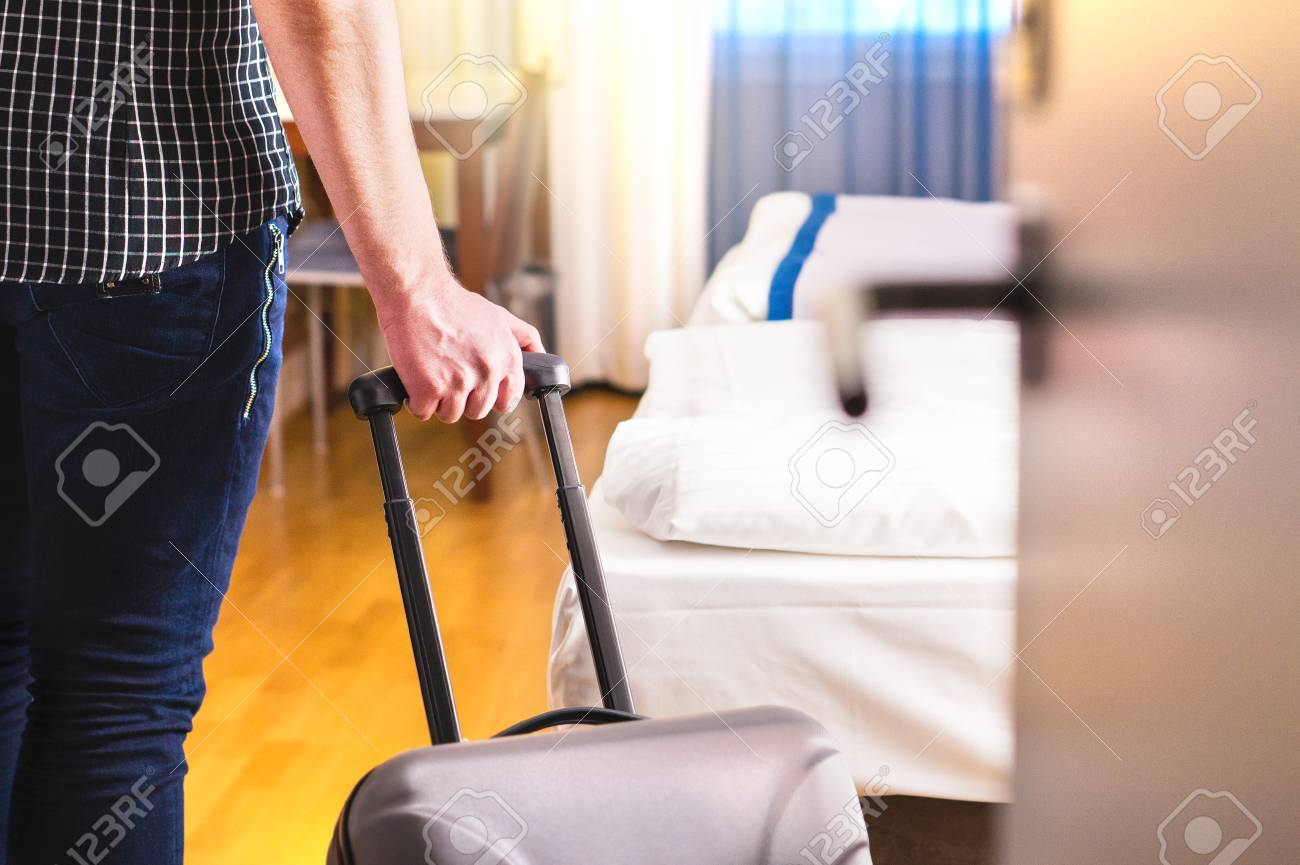 Man pulling suitcase and entering hotel room. Traveler going in to room or walking inside motel with luggage. Travel and holiday apartment rental concept. - 95852620