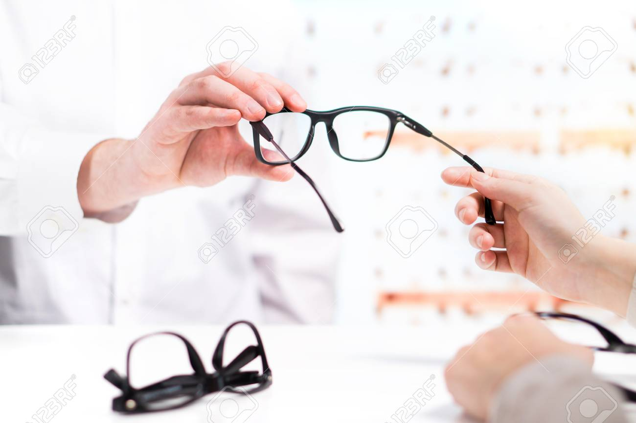 Optician giving new glasses to customer for testing and trying. Eye doctor with client comparing spectacles and choosing lenses in store. - 95852743